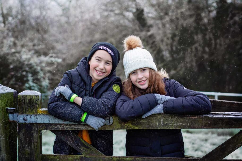 children leaning on fence
